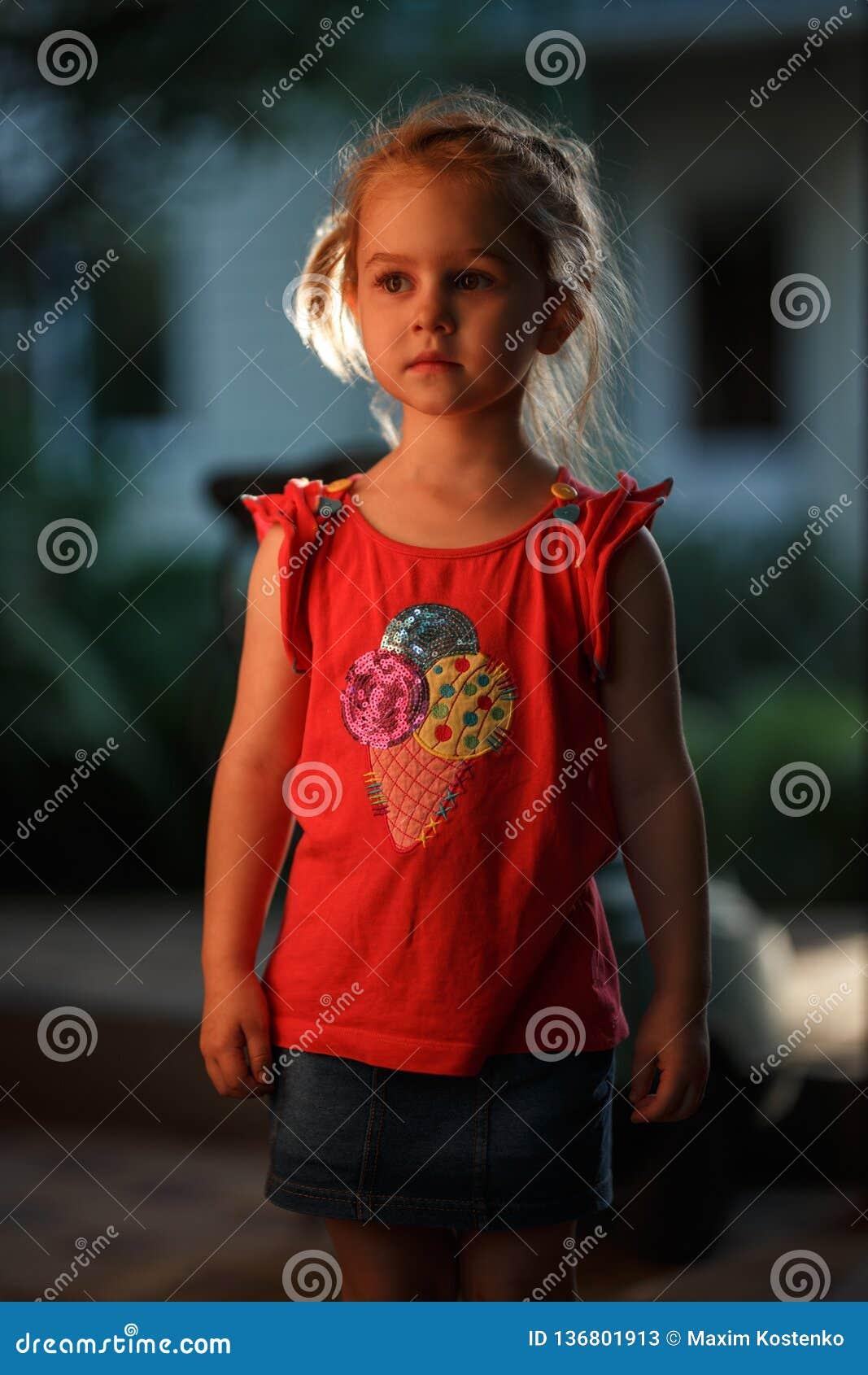 El retrato de un exterior de pelo rubio encantador de la situación de la muchacha en una tarde caliente del verano, el sol ilumin