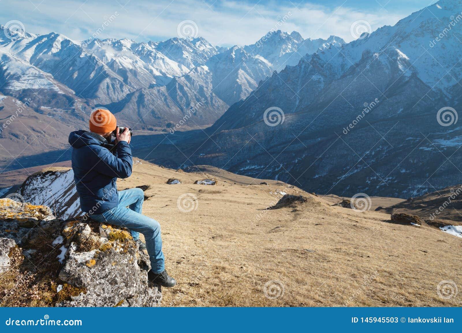 El retrato de un fotógrafo de sexo masculino barbudo en gafas de sol y de una chaqueta caliente con una mochila se sienta en una