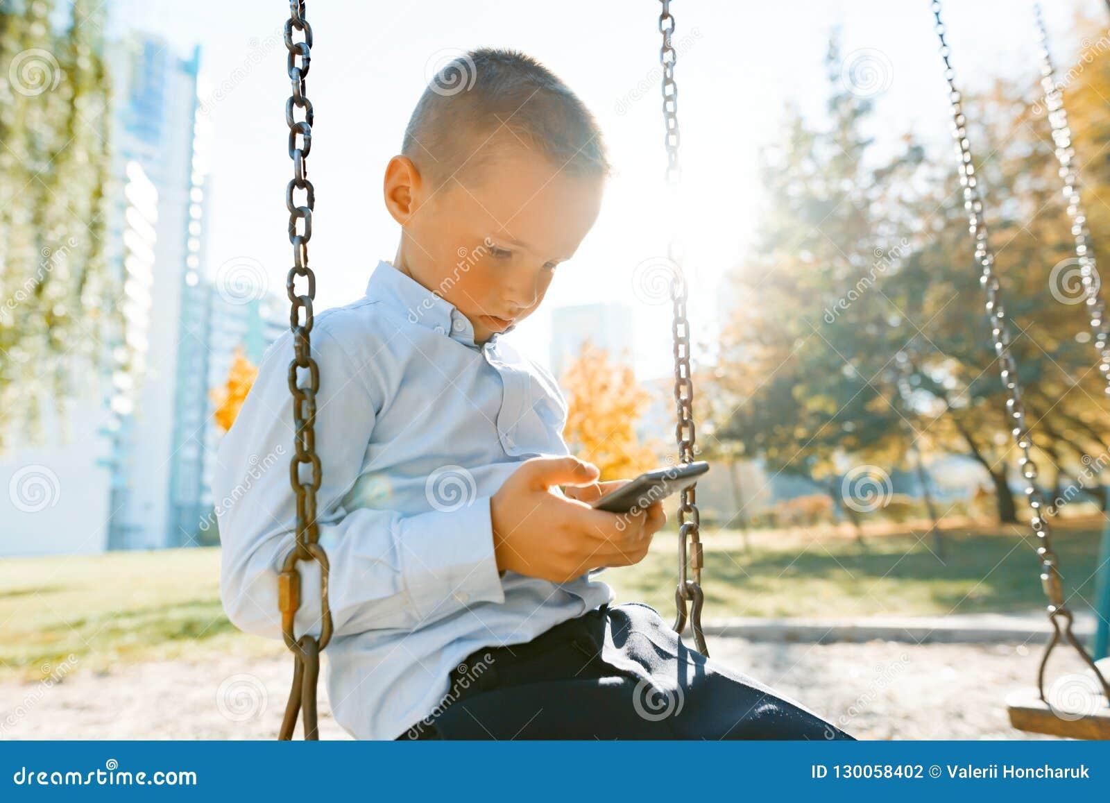 El retrato de un muchacho sonriente 6, 7 años, niño monta un oscilación en el parque del otoño, hora de oro