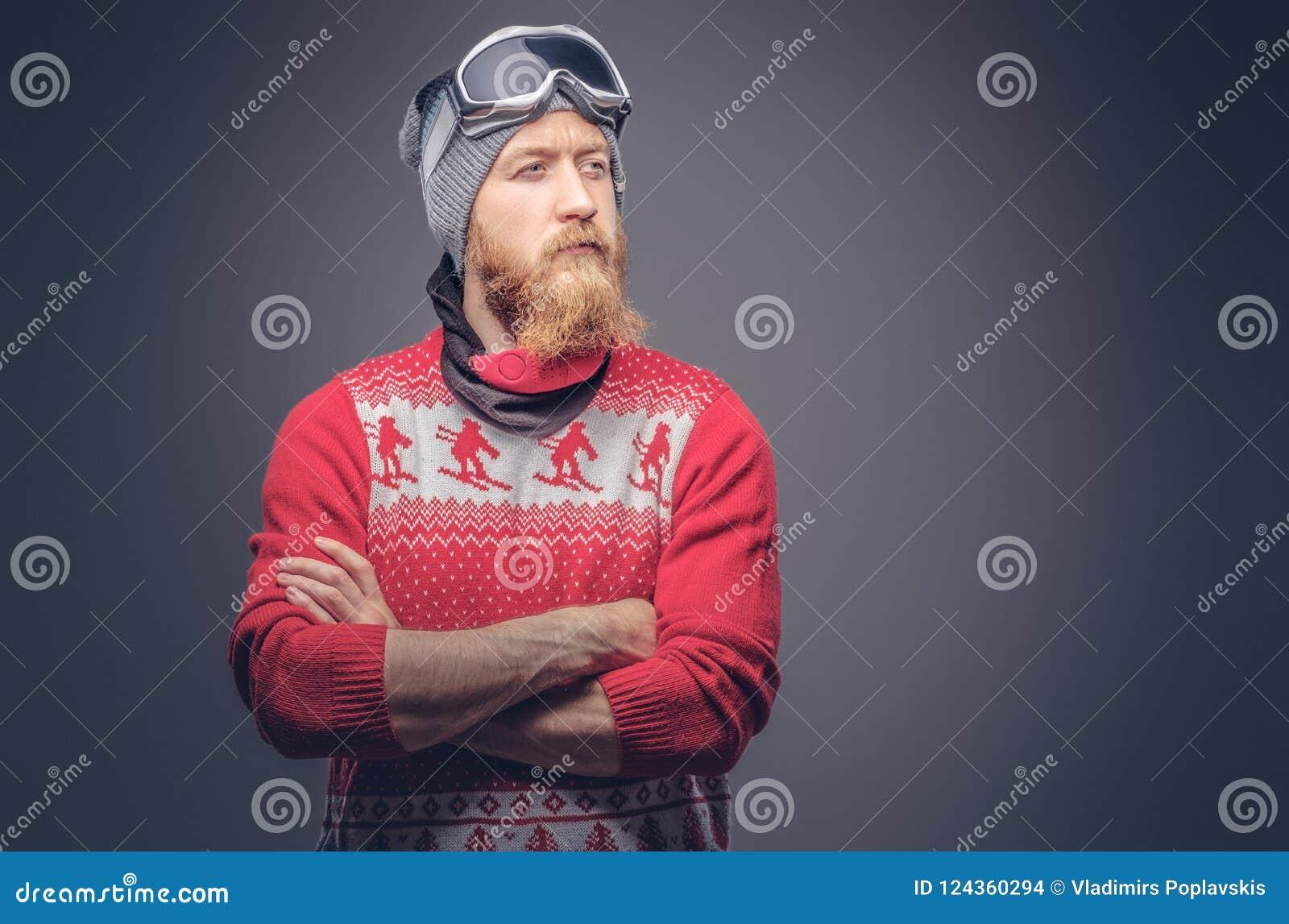 El retrato de un varón barbudo del pelirrojo brutal en un sombrero del invierno con los vidrios protectores se vistió en un suéte