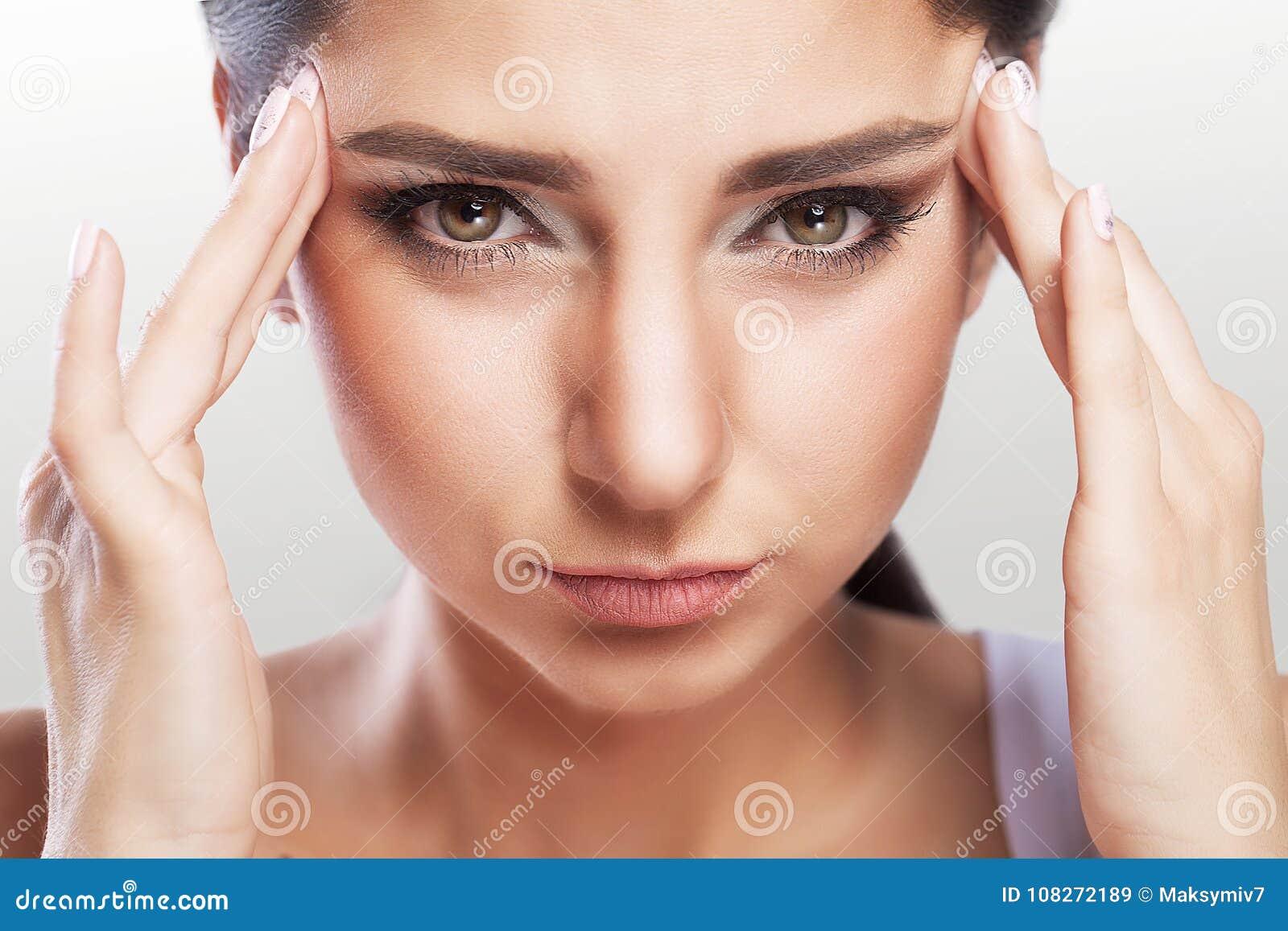El retrato de una morenita joven hermosa con un hombro desnudo, siente el gran dolor de cabeza, problemas de salud, jaqueca, maqu