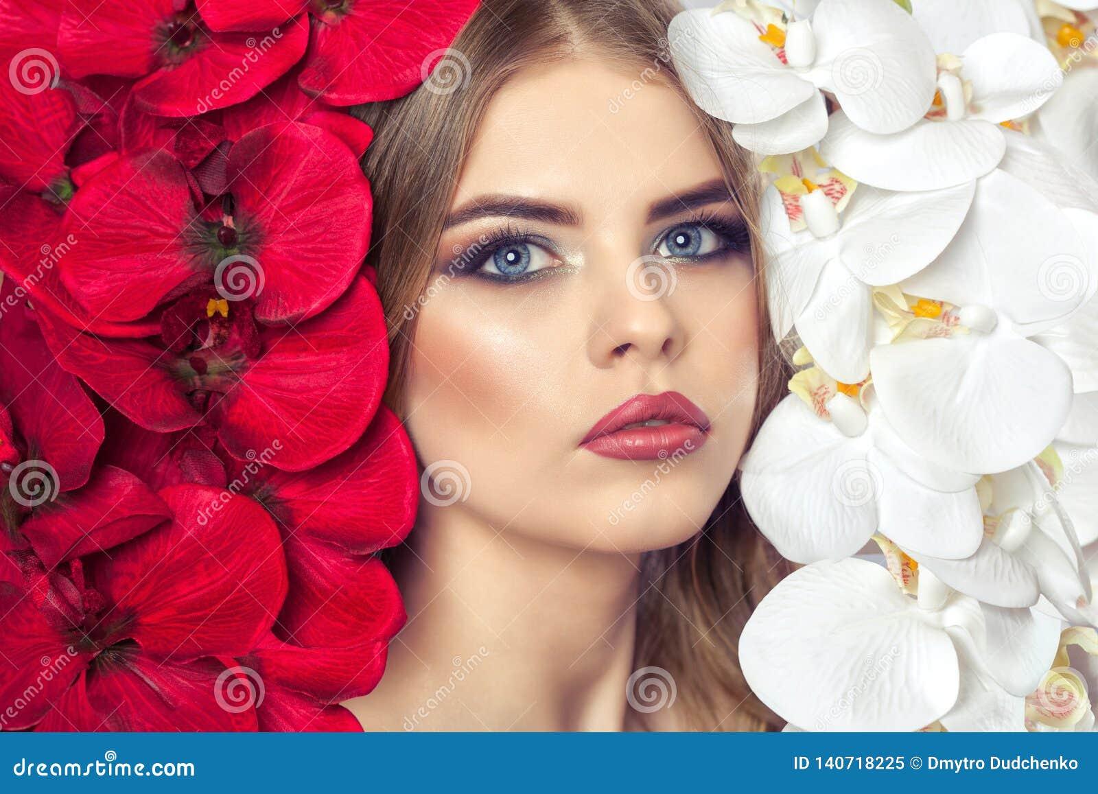 El retrato de una mujer con maquillaje hermoso sostiene una orquídea blanca y roja en sus manos