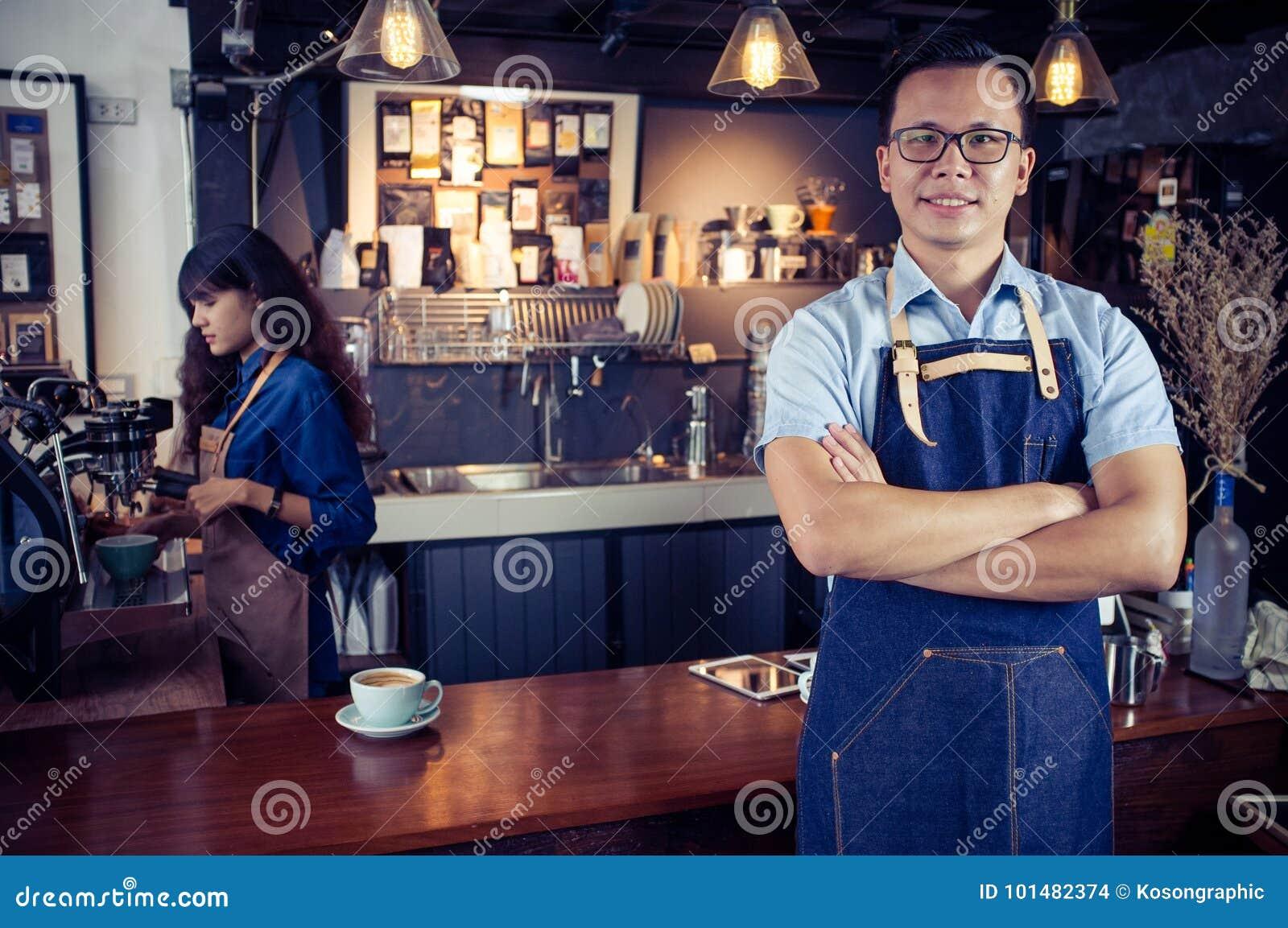 El retrato del barista asiático con los brazos cruzó en el contador en café