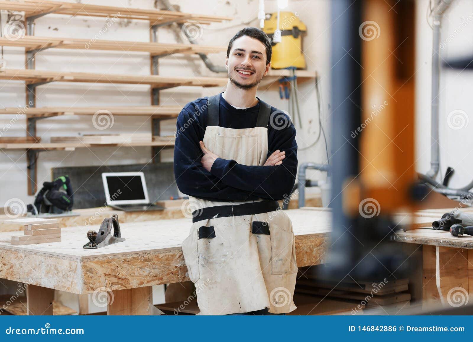El retrato del carpintero en ropa de trabajo delante del banco de trabajo Retrato del hombre sonriente en el trabajo en taller de