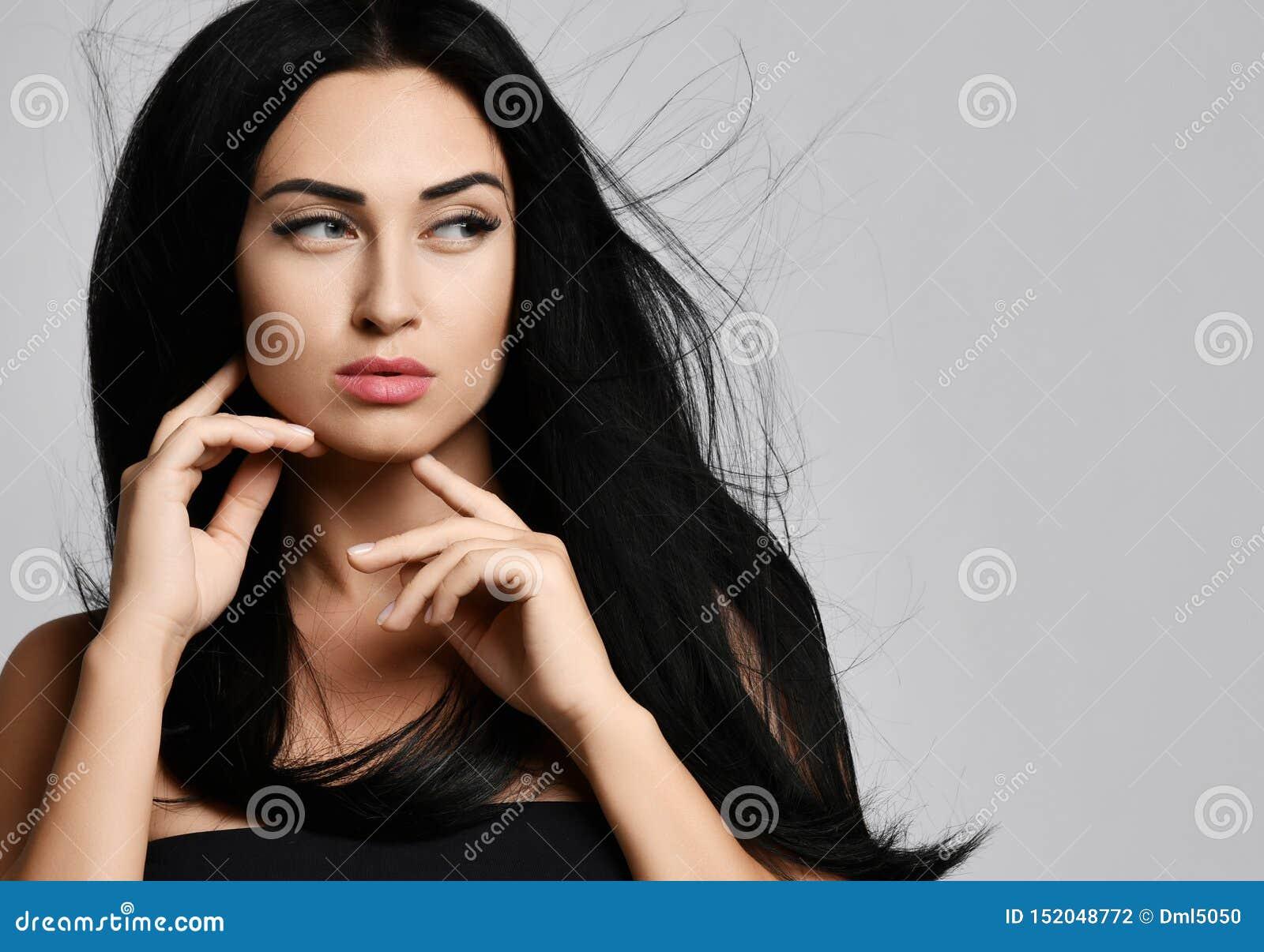 El retrato del concepto del anuncio de la morenita de la mujer con el pelo que agita en el viento toca su barbilla con la parte p