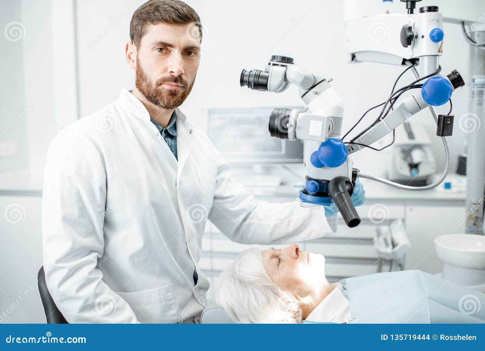 El retrato del dentista con un microscopio