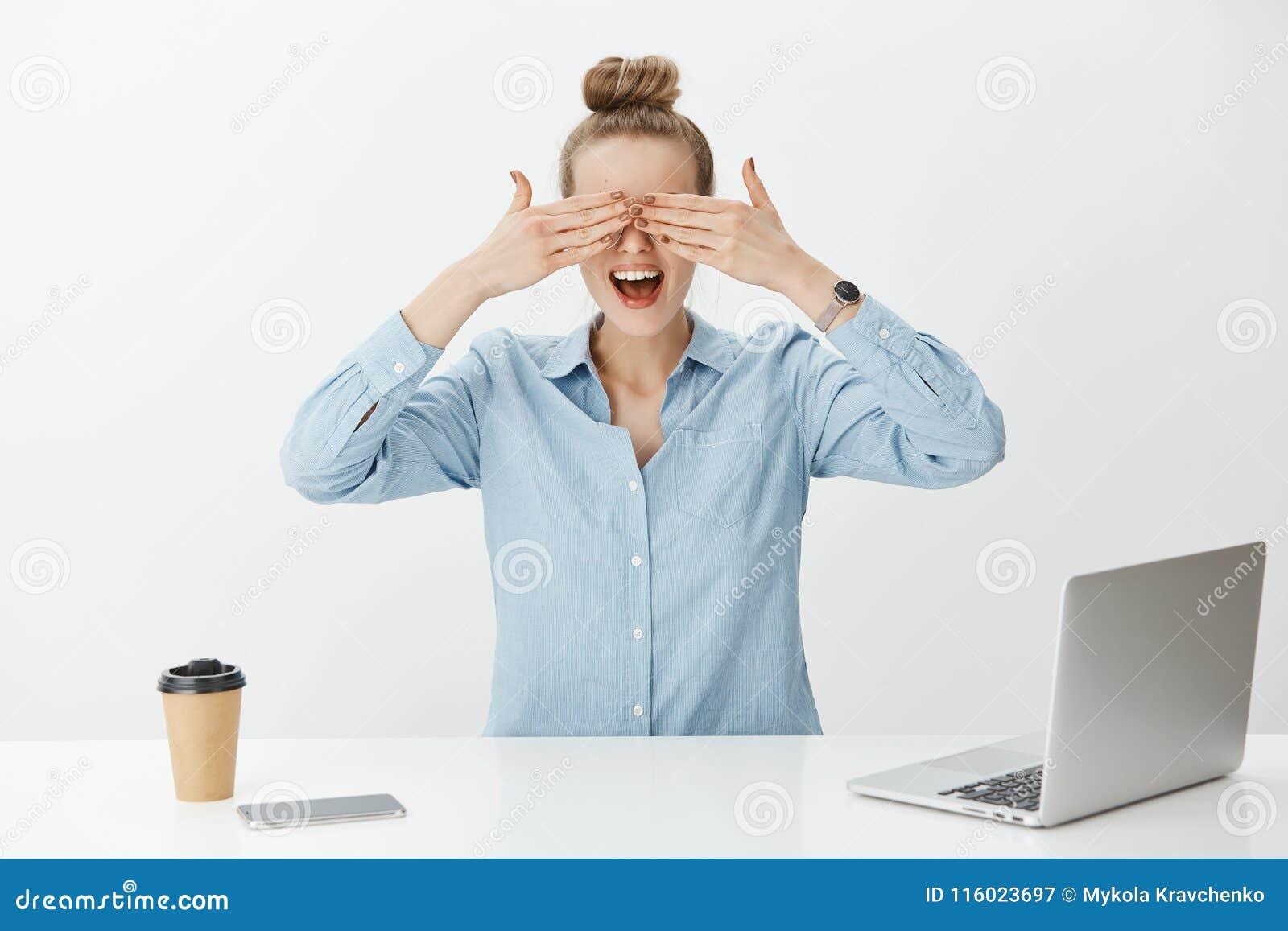 El retrato del empresario de sexo femenino apuesto sorprendente en oficina, cubriendo observa con las palmas y esperar impaciente
