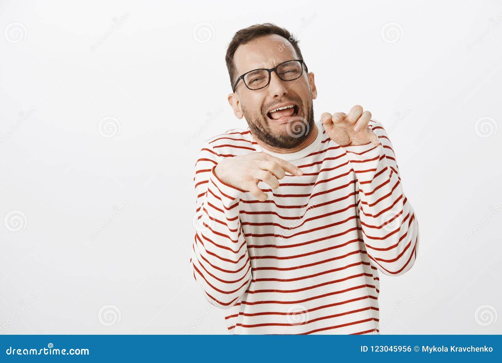 El retrato del hombre emotivo divertido en los vidrios que hacen caras y que imitan las patas del dinosaurio con entrega el pecho