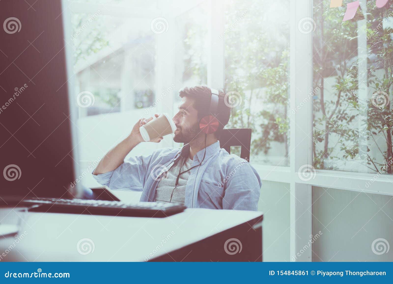 El retrato del hombre hermoso con café de consumición de la barba y el escuchar la música en línea en el hogar moderno, feliz y l