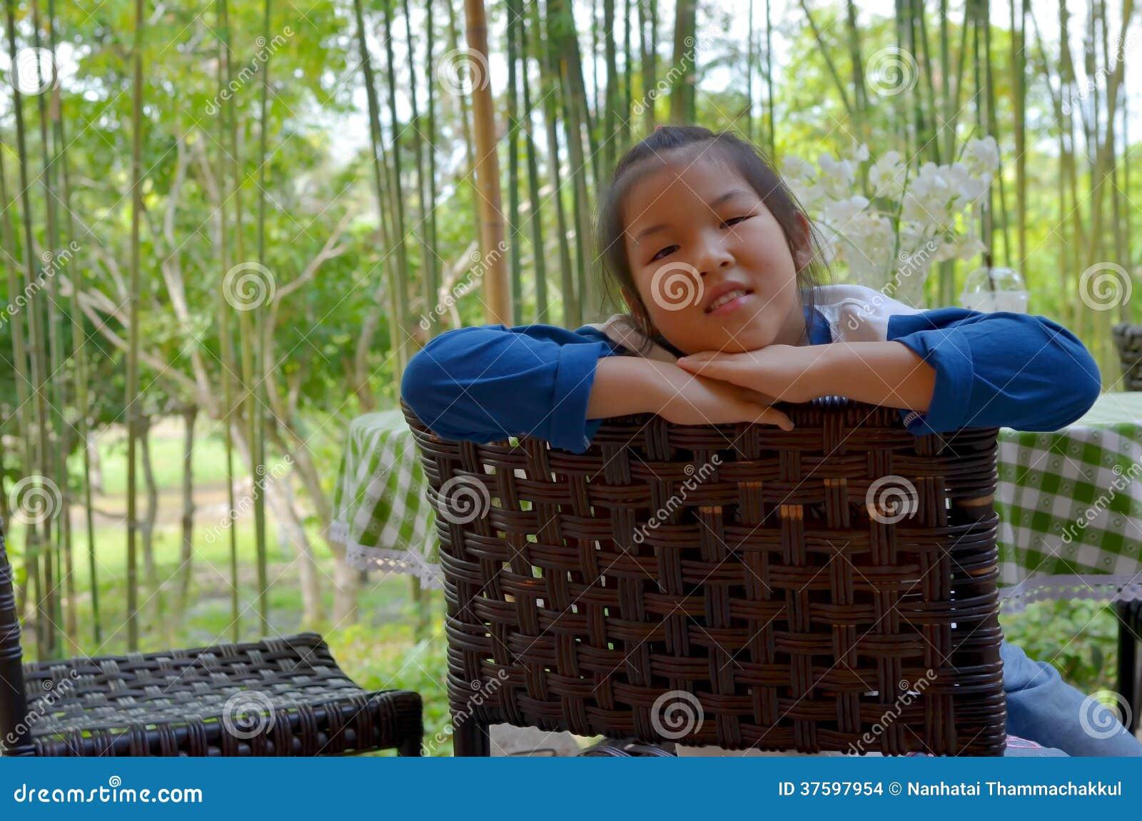 El retrato del primer de la muchacha asiática se sienta en silla