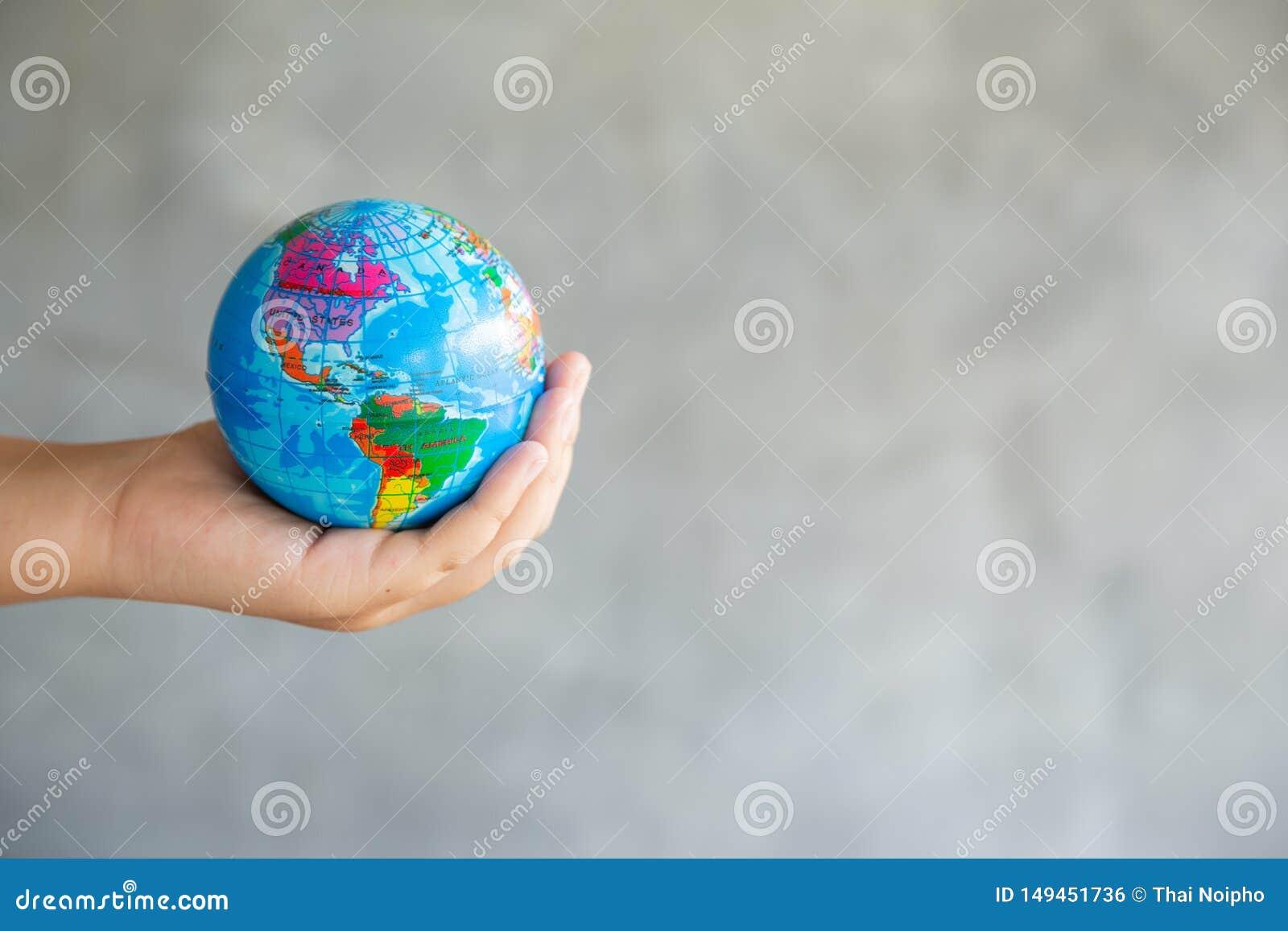 El retrato del primer de la mujer se est? considerando global en sus manos en fondo gris Salvo el planeta y viajar conceptuales