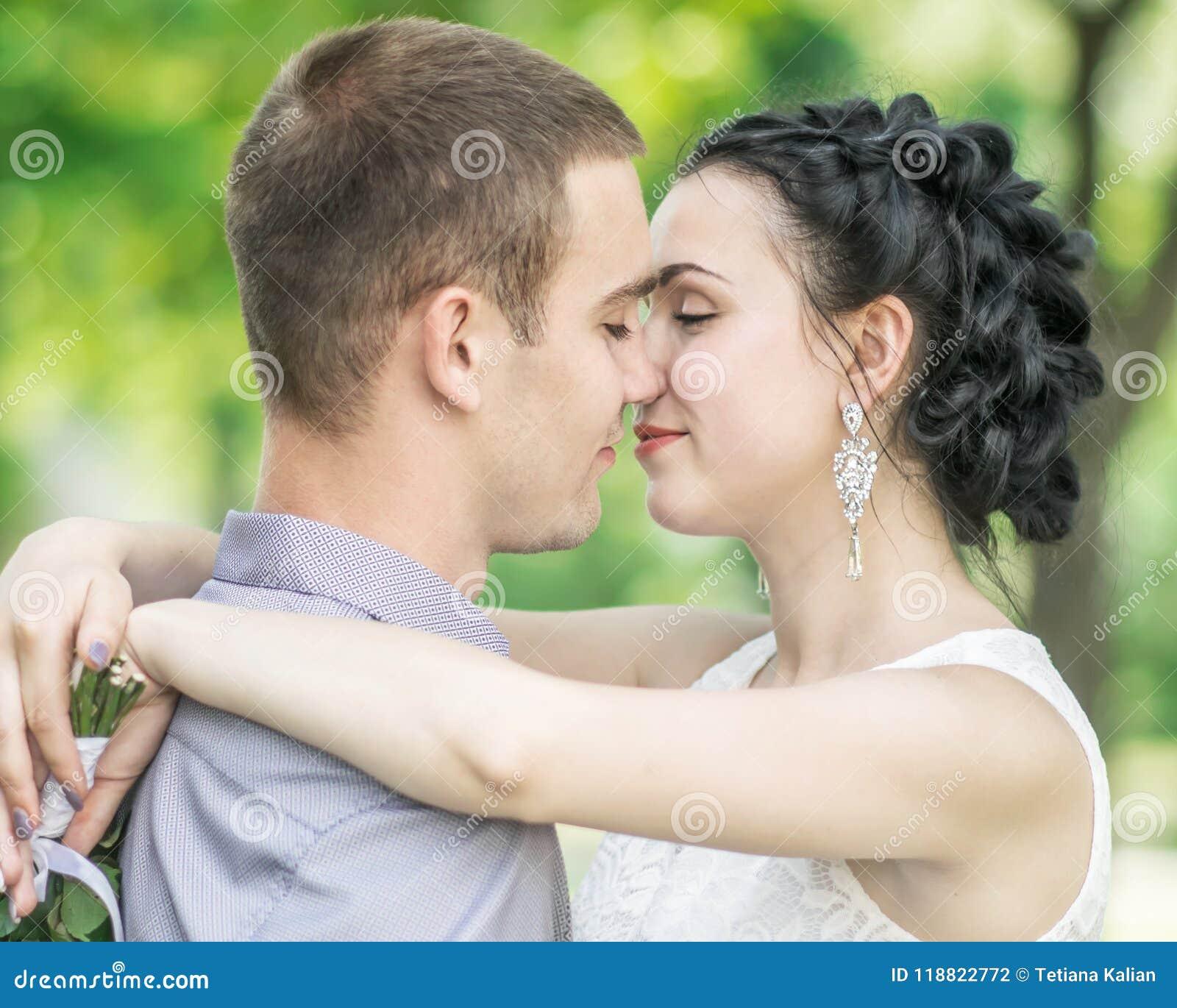 El retrato del primer de la novia femenina de los pares jovenes hermosos y el novio del varón que se besa en verano parquean Espo