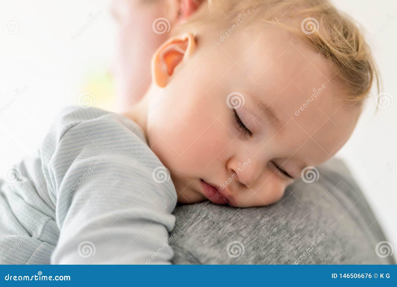 El retrato del primer del ni?o peque?o cauc?sico rubio adorable lindo que duerme en padres lleva a hombros dentro Sensaci?n dulce