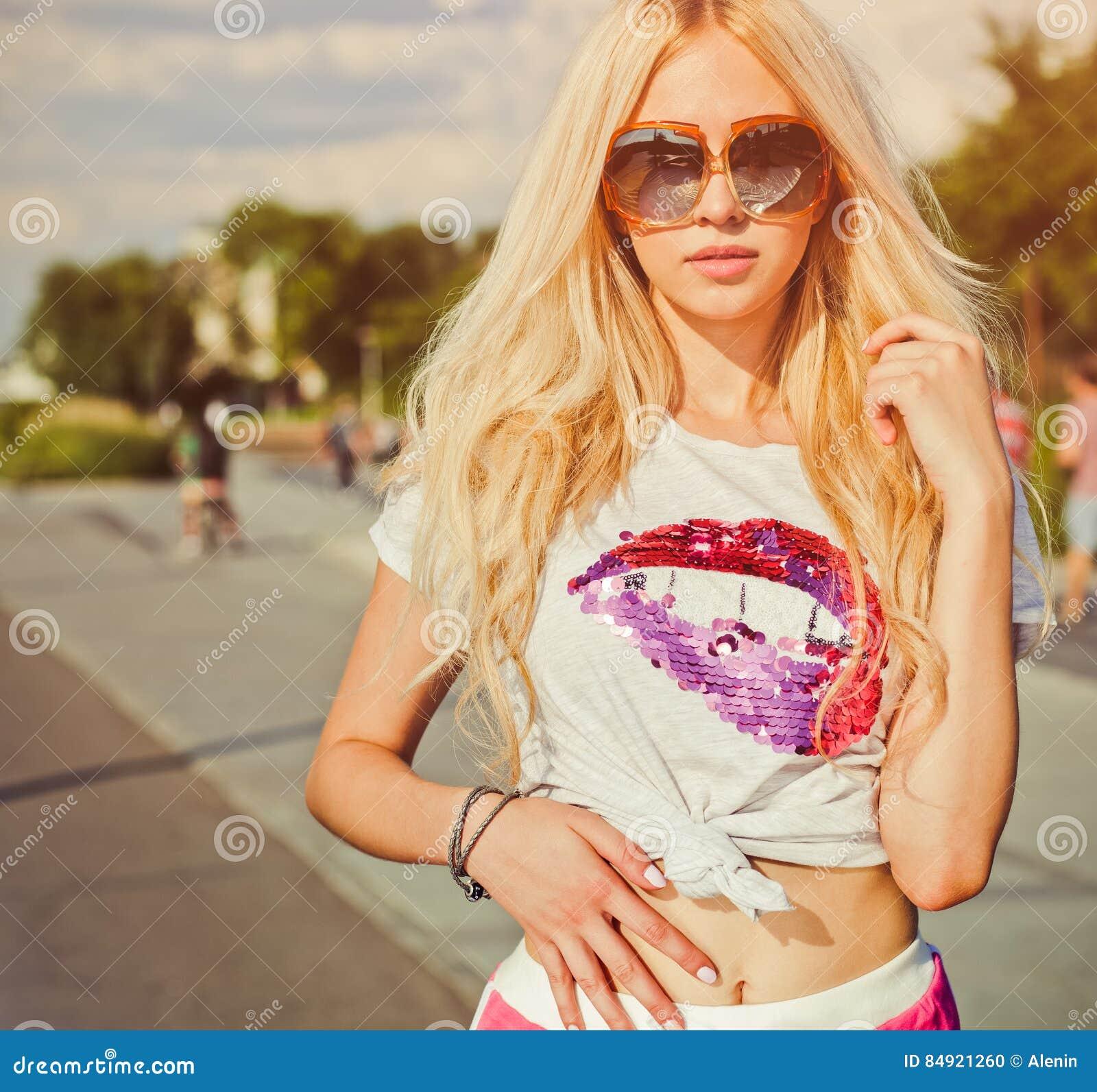 El retrato del verano de la mujer atractiva joven en camiseta del vintage, los pantalones cortos rojos y las gafas de sol que pre