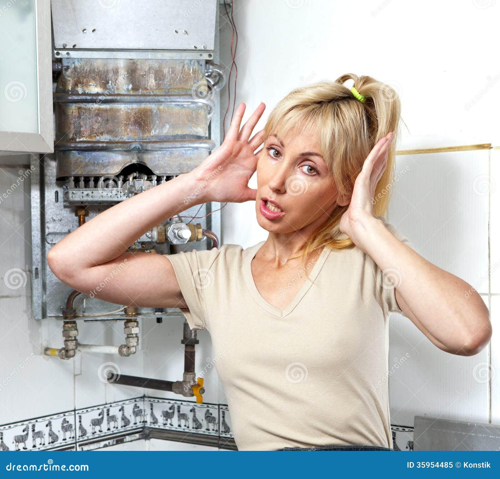 El retrato la mujer joven está trastornado por ése que el calentador de agua del gas se ha roto