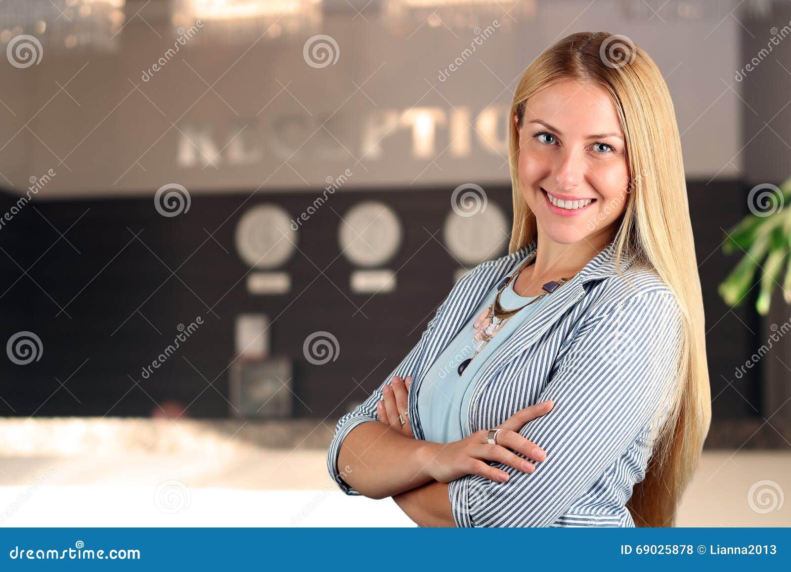 El retrato sonriente hermoso de la mujer de negocios Recepcionista de sexo femenino sonriente
