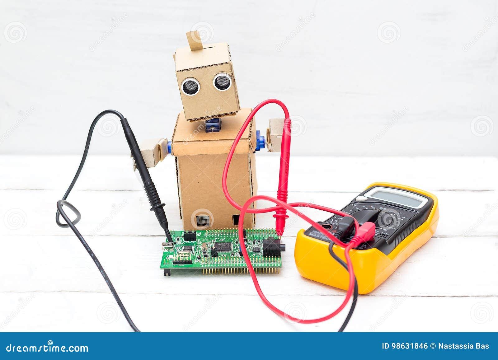 El robot sostiene un voltímetro en sus manos y un circuito impreso b