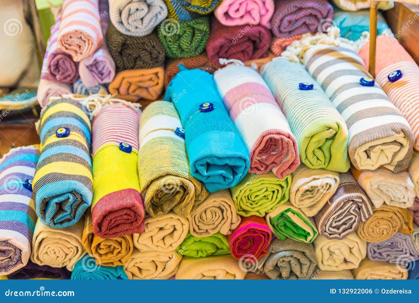 El rollo formó la seda, las bufandas de la cabeza de la cachemira o los mantones coloridos tradicionales apilados