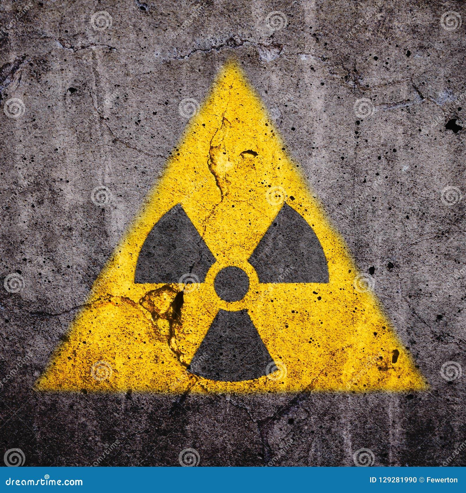 El símbolo amonestador del peligro atómico radiactivo de la radiación ionizante en forma amarilla triangular pintó el muro de cem
