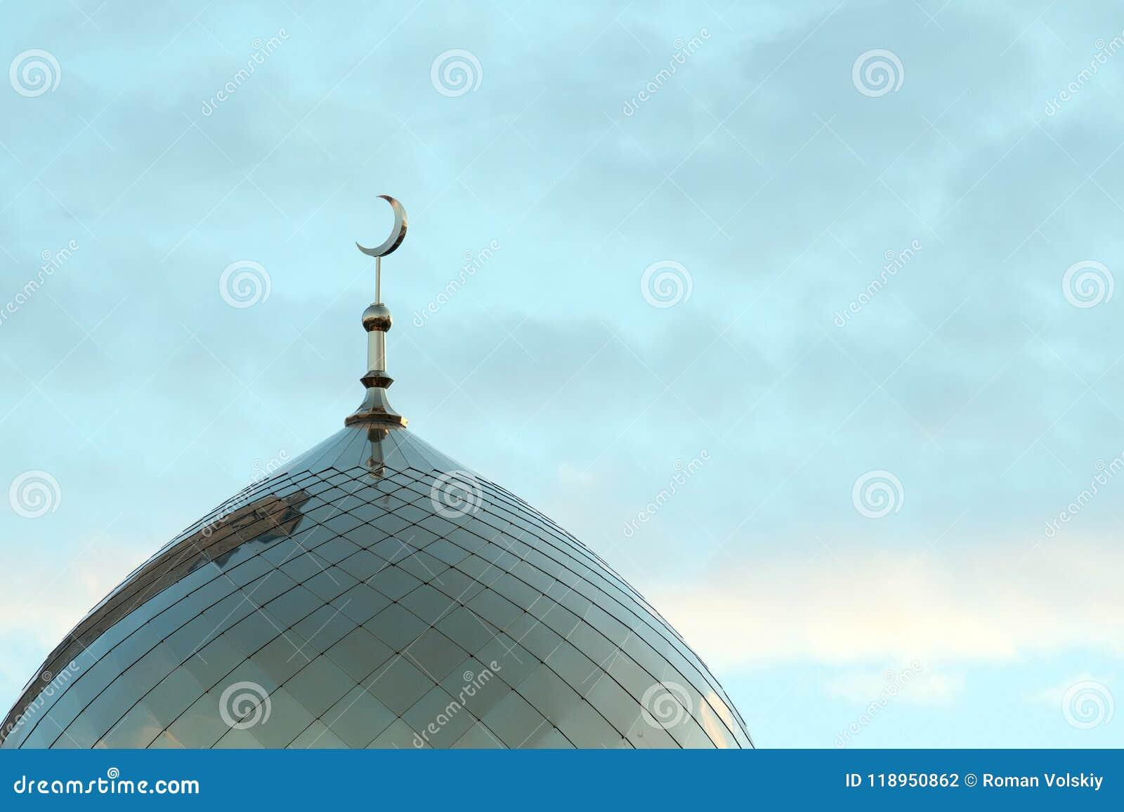 El símbolo del Islam es una luna creciente de oro encima del alminar de la mezquita en el cielo azul de la mañana con las nubes