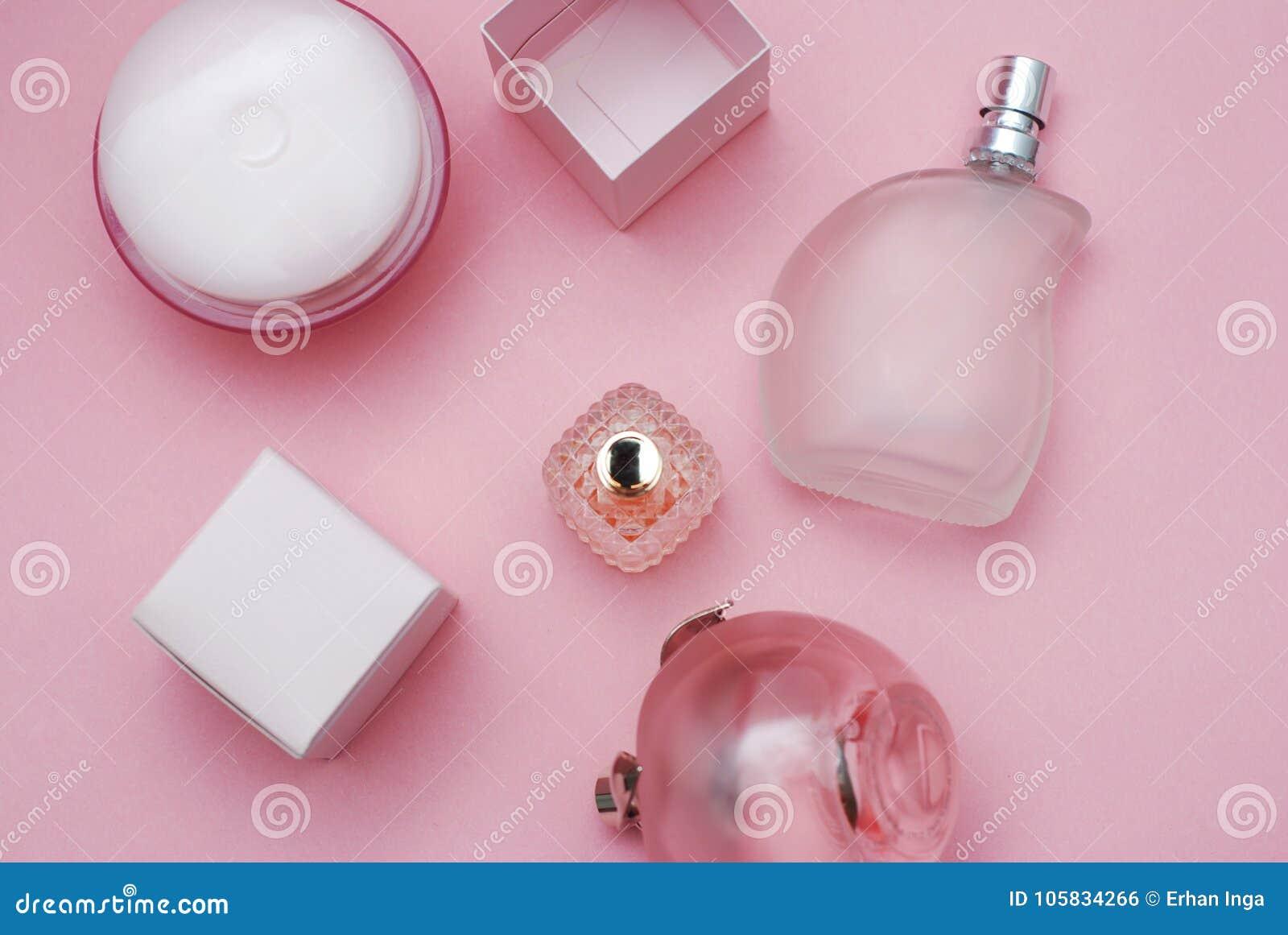 El ` s de las mujeres perfuma Botles y los cosméticos en botella de cristal hermosa y en fondo rosado Concepto de la moda y de la