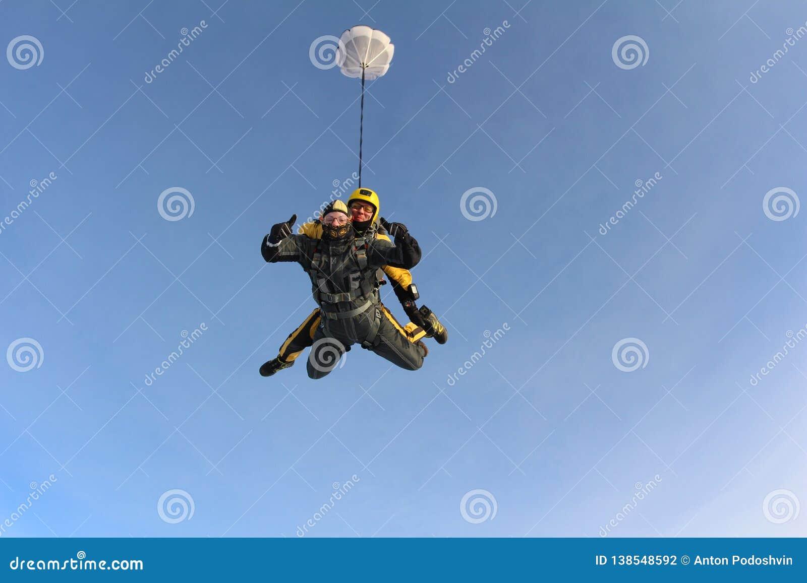 El saltar en caída libre en tándem Los Skydivers están volando sobre las nubes blancas