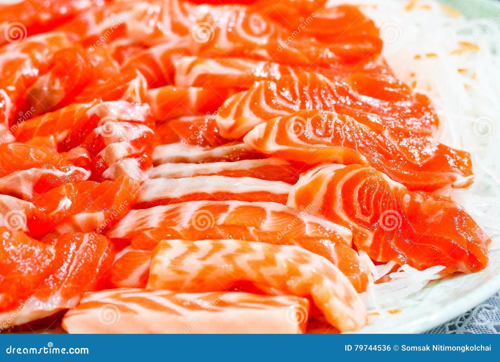 El sashimi de color salmón, cierre para arriba del modelo en salmones de la rebanada, seleccionó focu