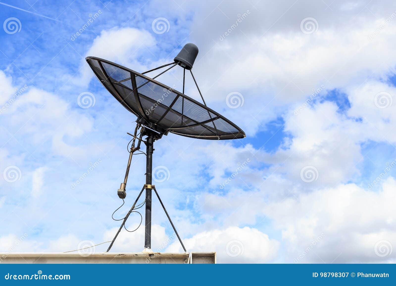 El satélite negro instala en el tejado de la casa con el cielo azul