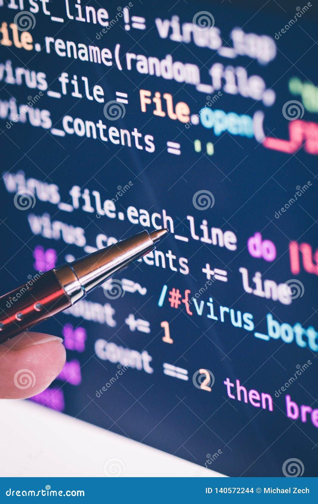 El señalar encendido codifica en software en la pantalla de ordenador con la pluma