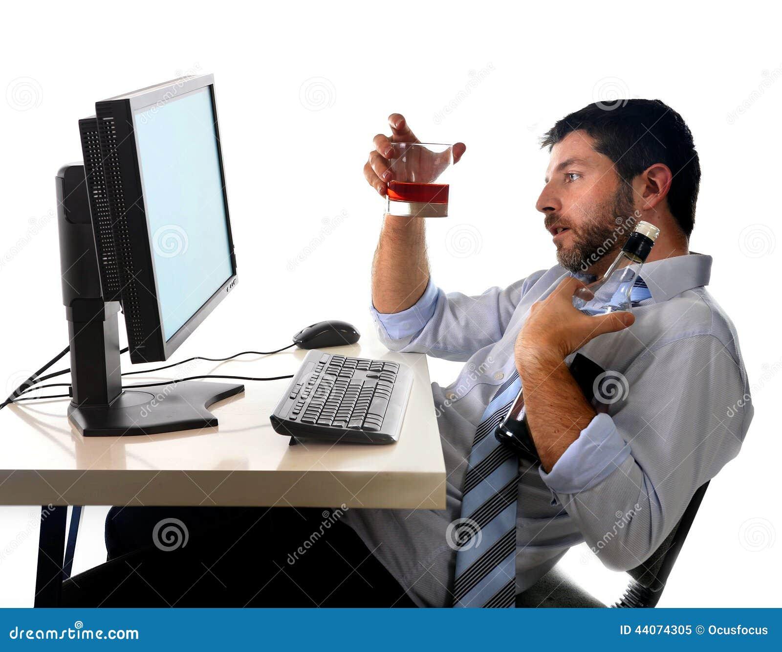 El sentarse de consumición alcohólico del whisky del hombre de negocios bebido en la oficina con el ordenador