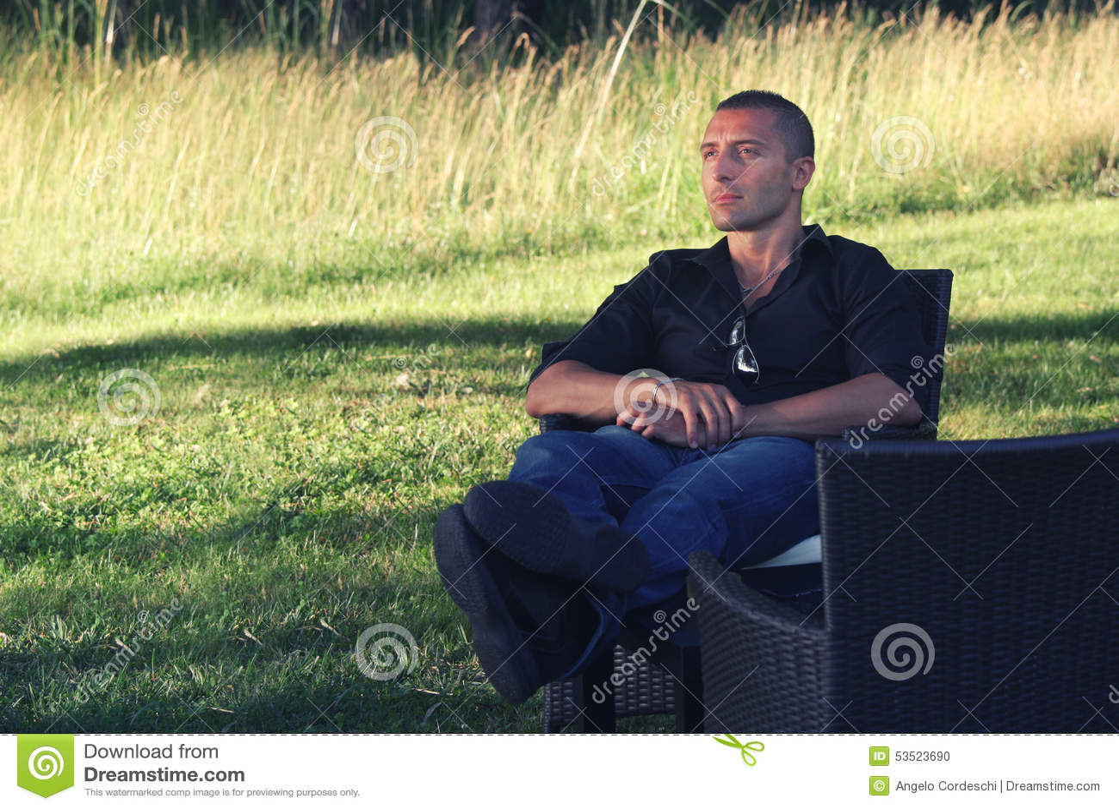 El sentarse de relajación del hombre en naturaleza Concepto de la relajación