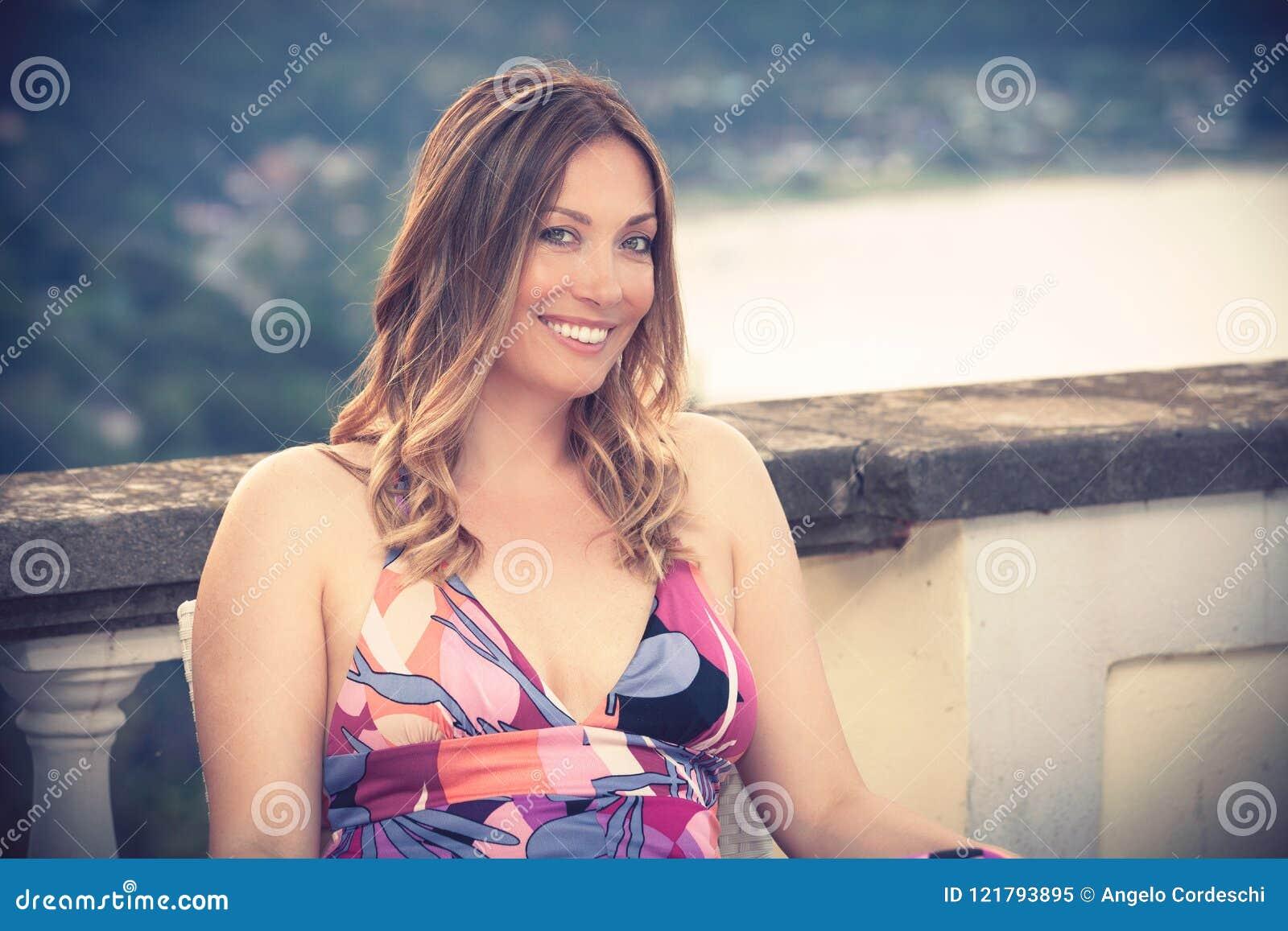 El sentarse sonriente hermoso y encantador de la mujer al aire libre