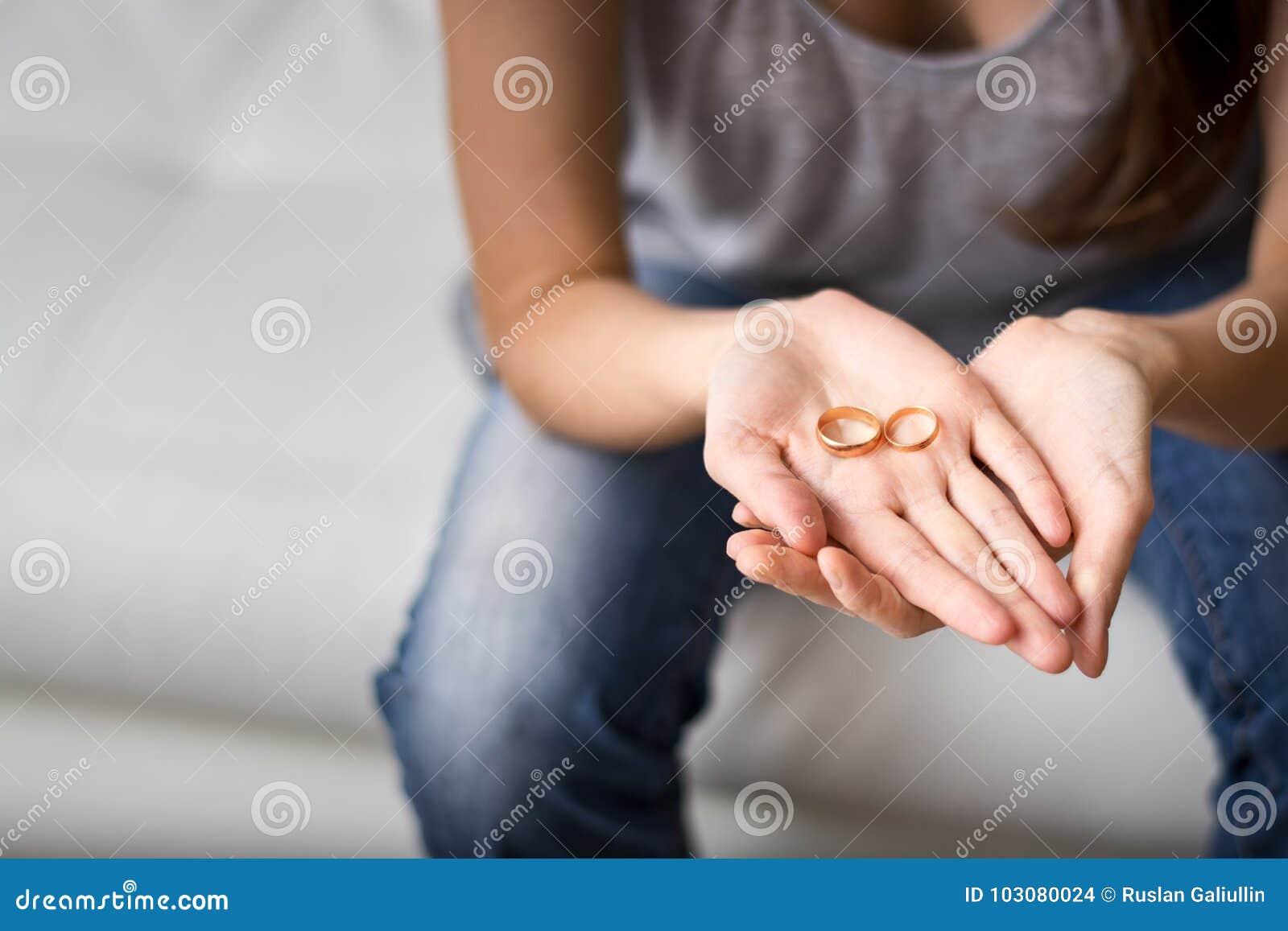 El ser esposa triste mira el anillo en la palma delante de él, nostálgico sobre un marido anterior, familia, boda El concepto de