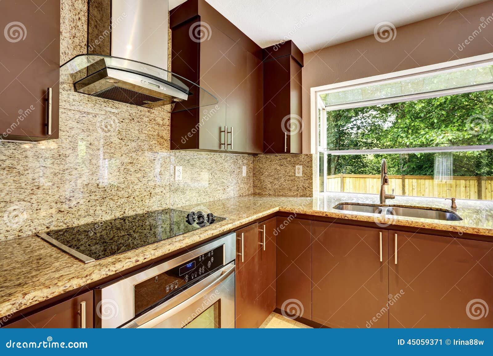 El sitio moderno de la cocina con los gabinetes marrones for Cocinas con gabinetes blancos