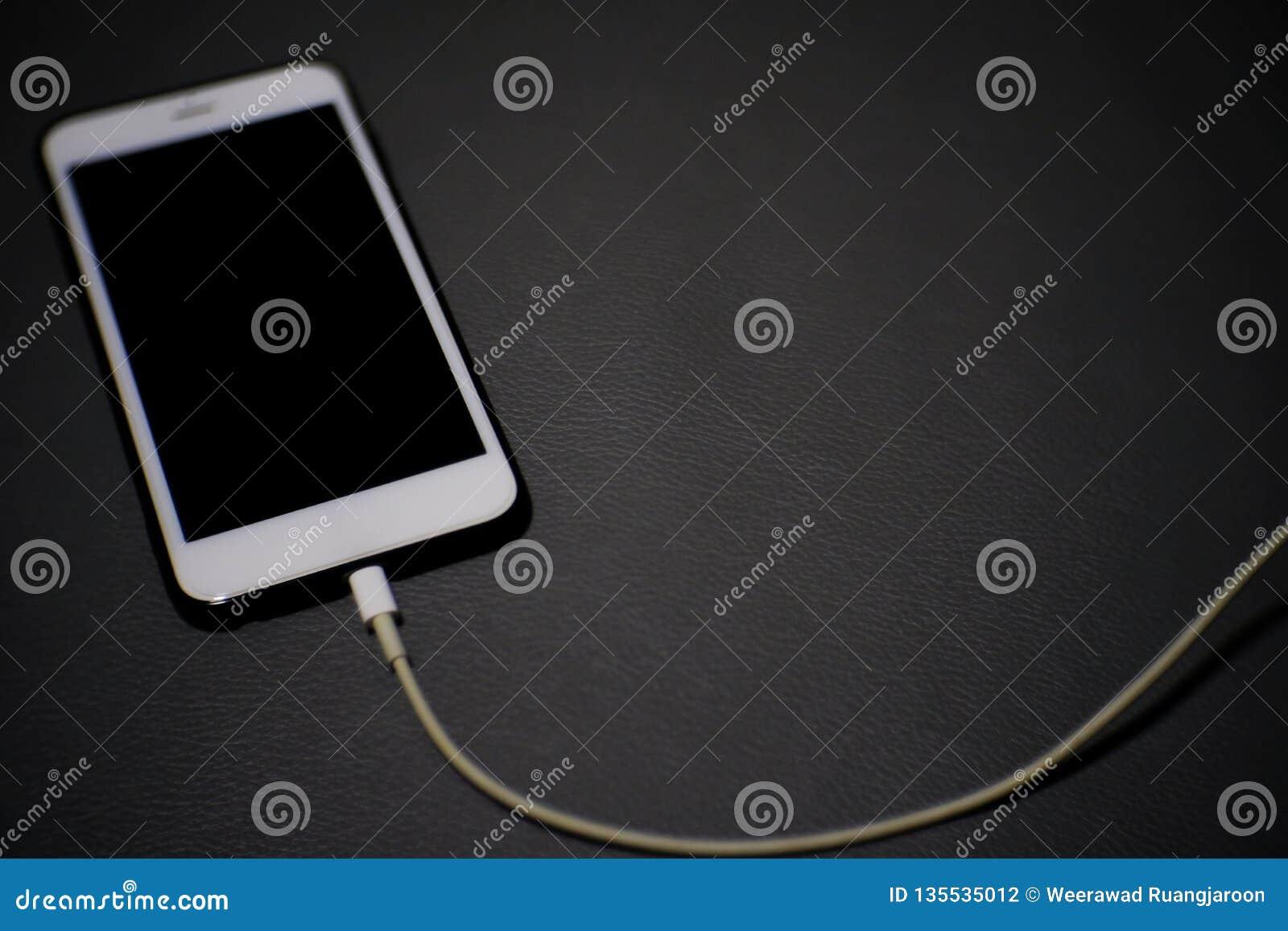 El smartphone móvil está cargando la batería en fondo gris