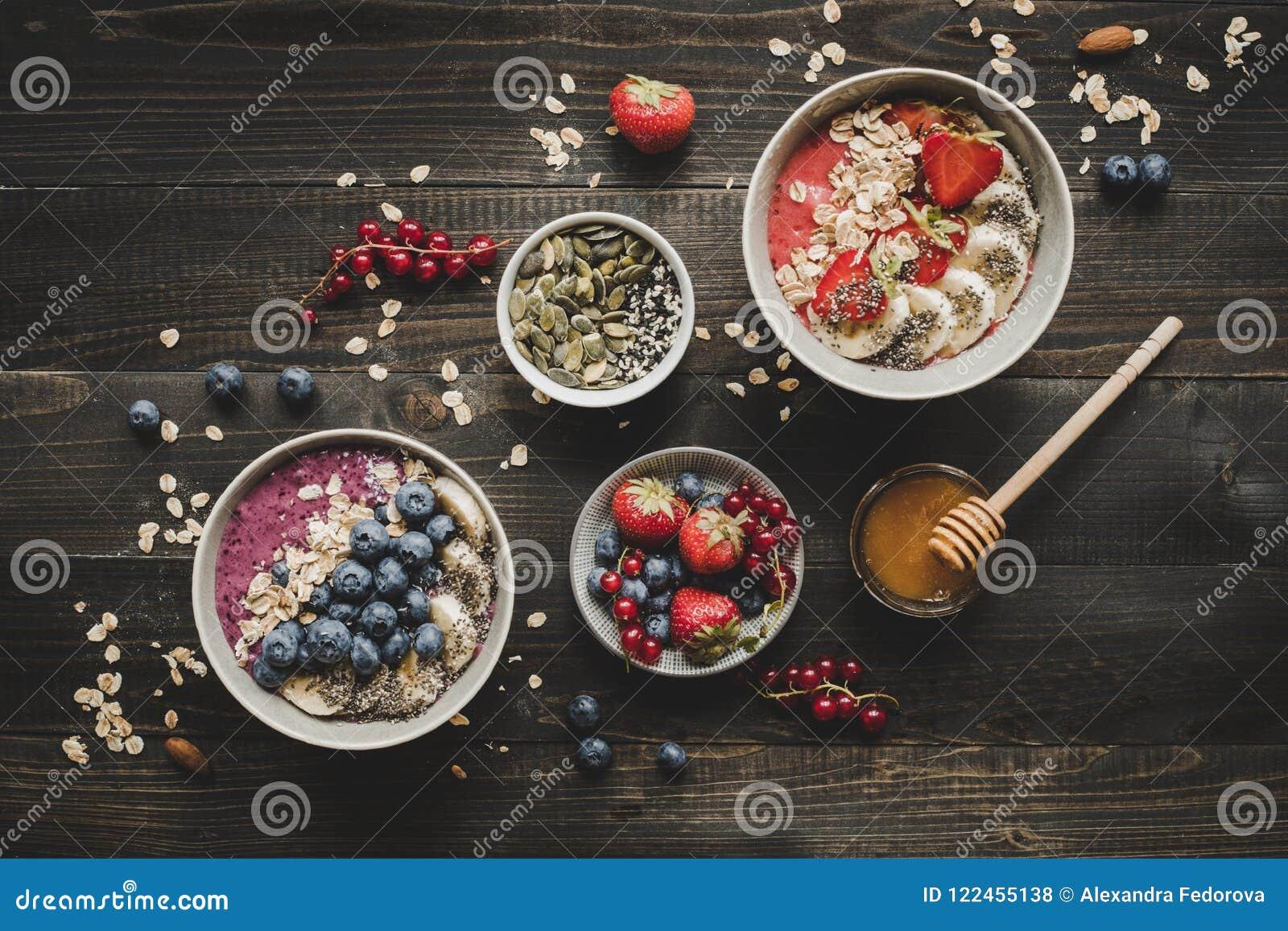 El smoothie delicioso del desayuno de Helthy rueda con las frutas, las bayas y las semillas en el fondo de madera