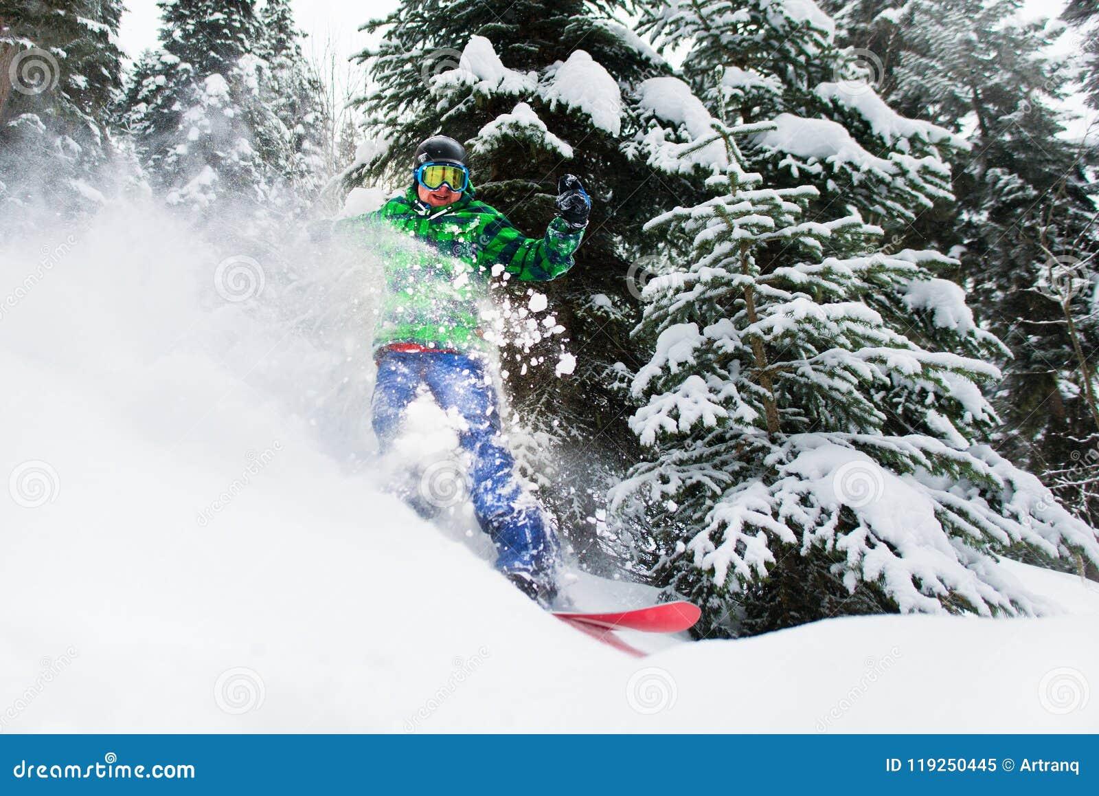 El snowboarder de sexo masculino alegre monta en el bosque que crea un espray de la nieve