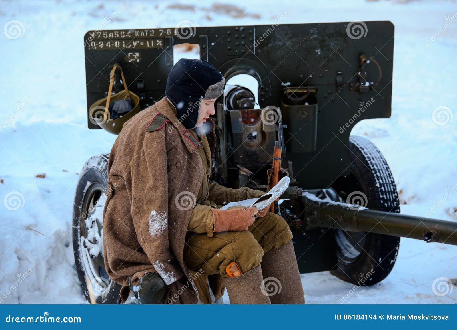 El soldado de ejército rojo está leyendo el periódico que se sienta en el arma divisional M1942 ZiS-3 de 76 milímetros