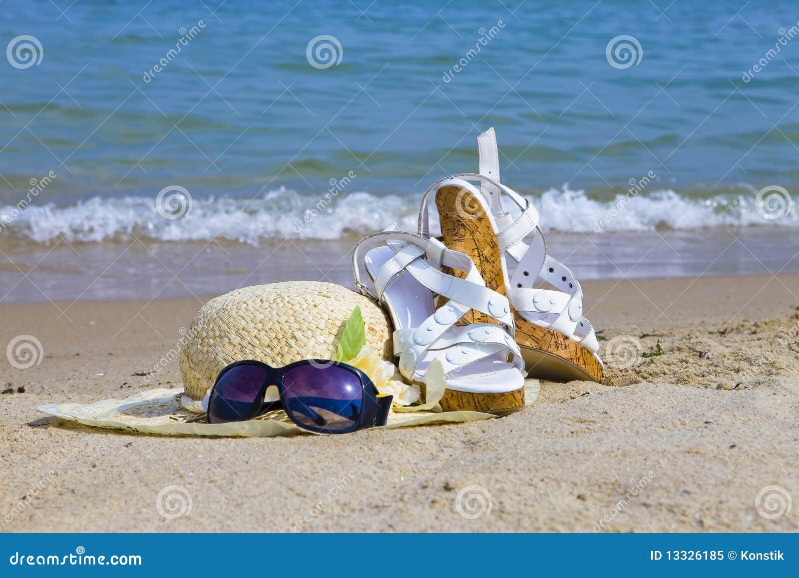 El sombrero de las gafas de sol, de paja y la sandalia ponen en la arena