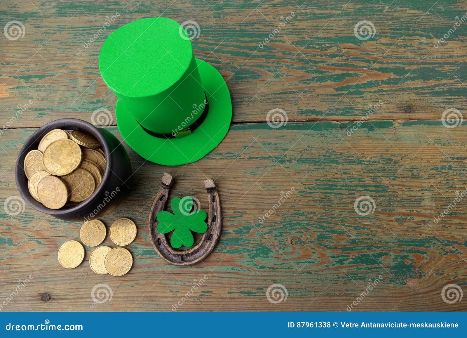 El sombrero feliz del duende del día del St Patricks con las monedas de oro y los encantos afortunados en vintage diseñan el fond