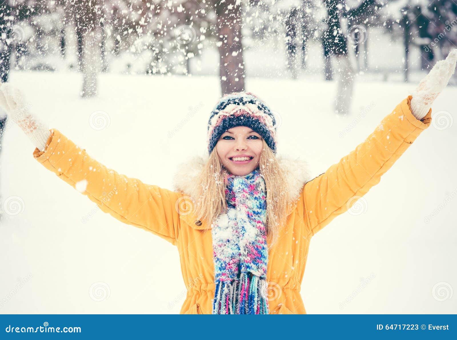 El sombrero que llevaba de la mujer joven y las manos sonrientes felices de la bufanda aumentaron al aire libre