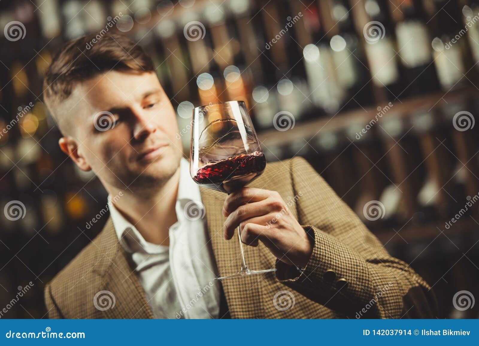 El Sommelier considera el vino tinto en bokal en el fondo de estantes con las botellas en sótano Color de apreciación masculino,