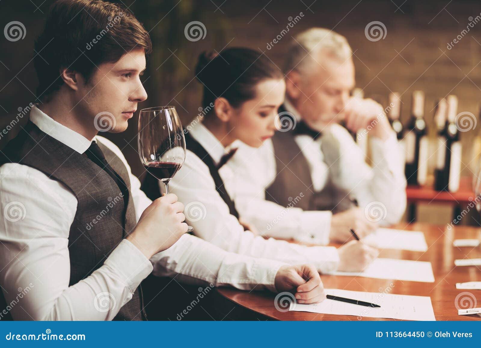 El sommelier experimentado explora el gusto del vino en restaurante El camarero joven prueba las bebidas alcohólicas