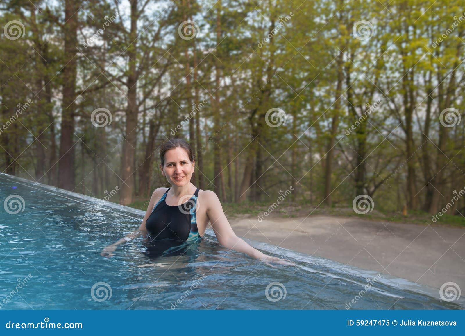 El soporte de la mujer en piscina al aire libre