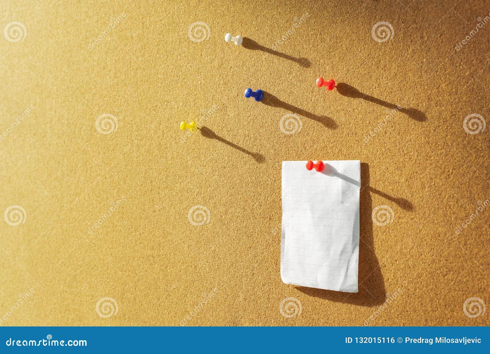 El tablero anaranjado del corcho con una nota del papel del boletín fijó y varios diversos pernos del color arriba Luz del sol ca