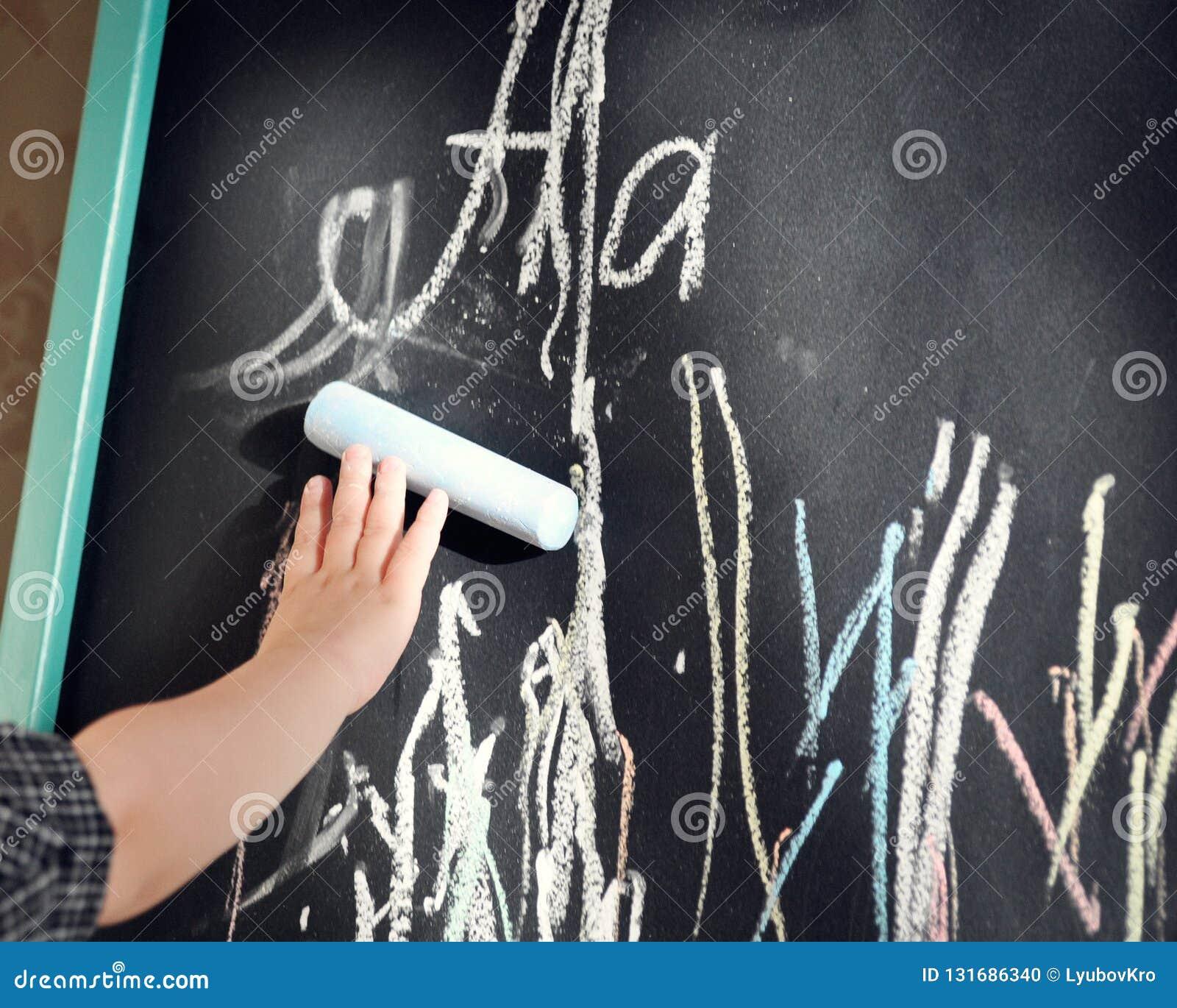 El tablero de tiza negro garabateó al niño pequeño coloreó los creyones Aprendizaje del alfabeto y preparación para la escuela