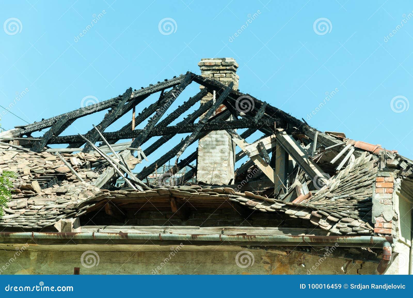 El tejado quemado de la casa civil abandonada en Ucrania del este dañó por la explosión de la granada en la zona de guerra