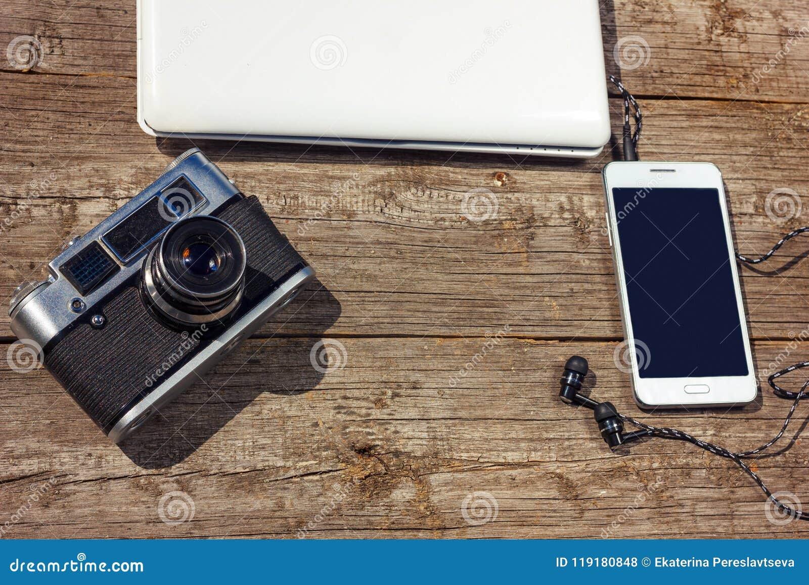 El teléfono y el ordenador portátil de la cámara están en una tabla de madera