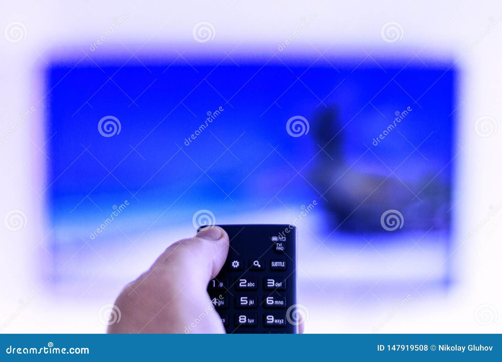 El teledirigido está en la mano de un hombre, dirigida a una TV en pantalla grande
