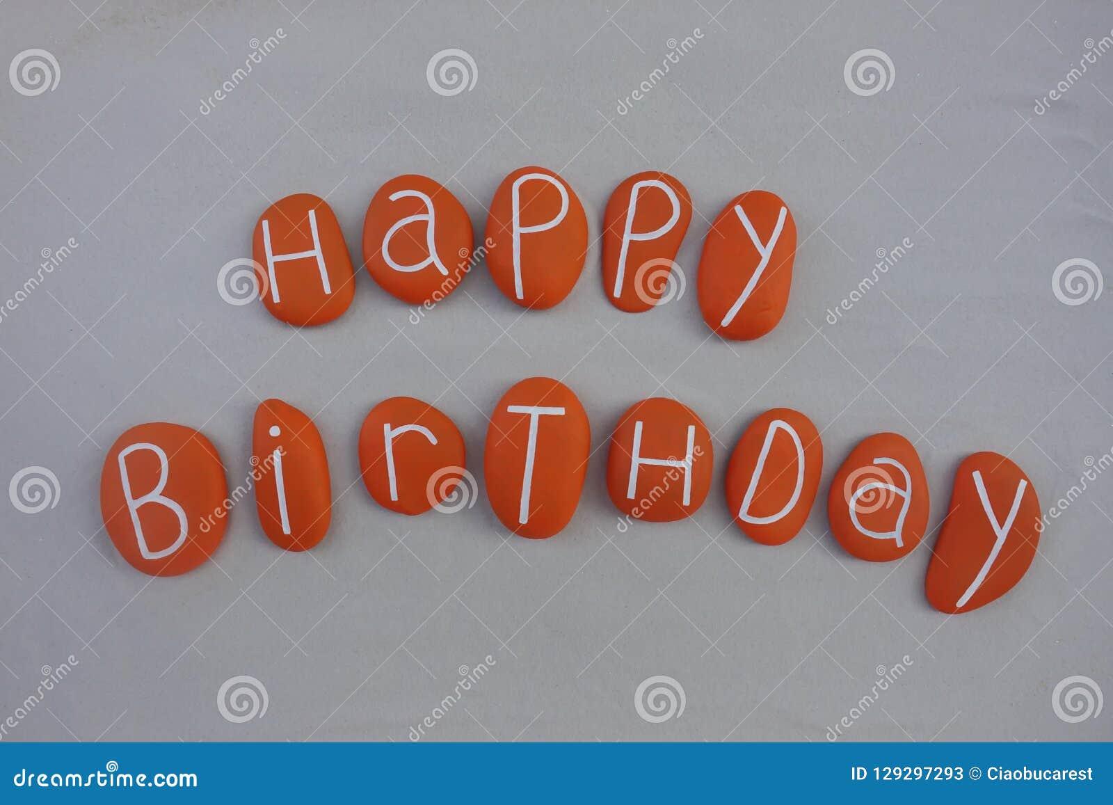 El texto del feliz cumpleaños con la naranja pintó piedras sobre la arena blanca